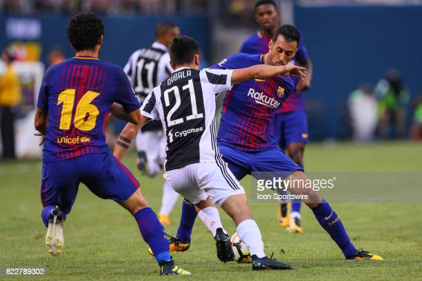 Juventus forward Paulo Dybala nutmegs Barcelona midfielder Sergio Busquets during the second half of the International Champions Cup soccer game...