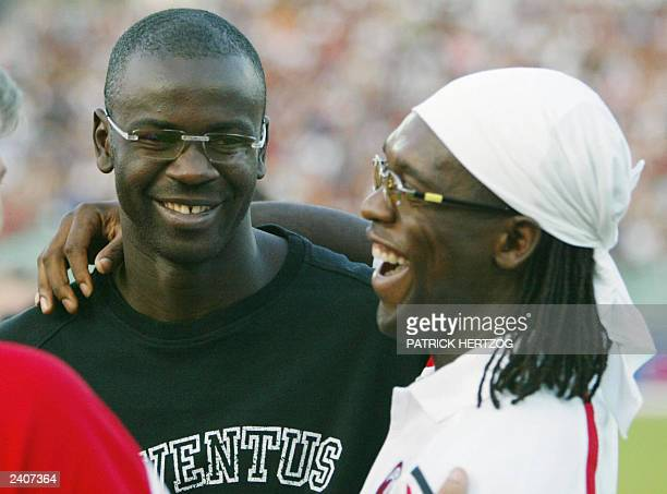 Juventus French defender Lilian Thuram jokes with Milan AC midfielder Clarence Seedorf12 August 2003 in 'del Conero' stadium in Ancona before the...