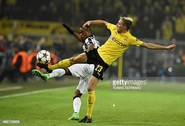 Juventus' French defender Patrice Evra and Dortmund's Slovenian midfielder Kevin Kampl vie for the ball during the Round of 16 secondleg UEFA...