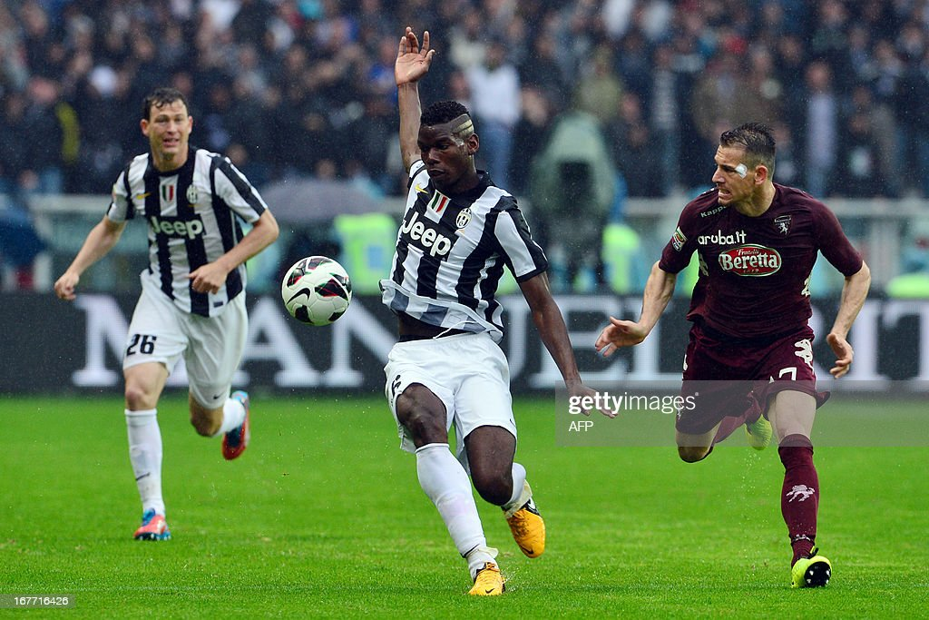 Juventus' French midfielder Paul Pogba (C) tries to control the ball in front of Torino's defender Salvatore Masiello during an Italian Seria A football match between Torino and Juventus at the Olympic Stadium in Turin on April 28, 2013.