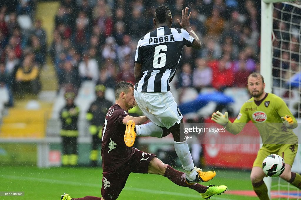 Juventus' French midfielder Paul Pogba (C) vies for the ball with Torino's Italian defender Salvatore Masiello during the Italian Serie A football match between Torino and Juventus on April 28, 2013 at the Olympic Stadium in Turin.