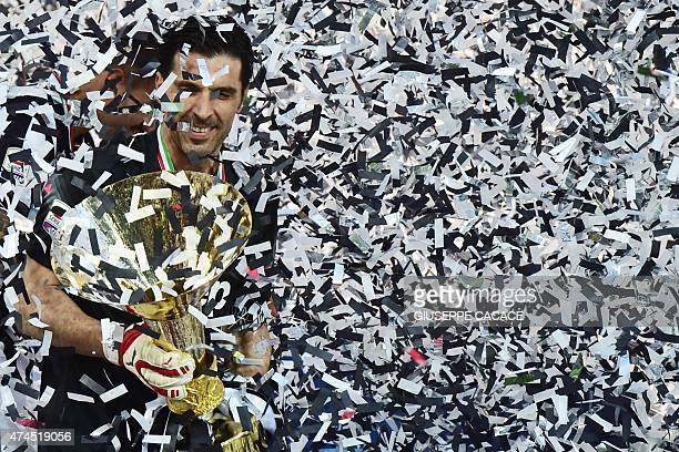 Juventus' goalkeeper and captain Gianluigi Buffon celebrates with the Italian League's trophy during a ceremony following the Italian Serie A...
