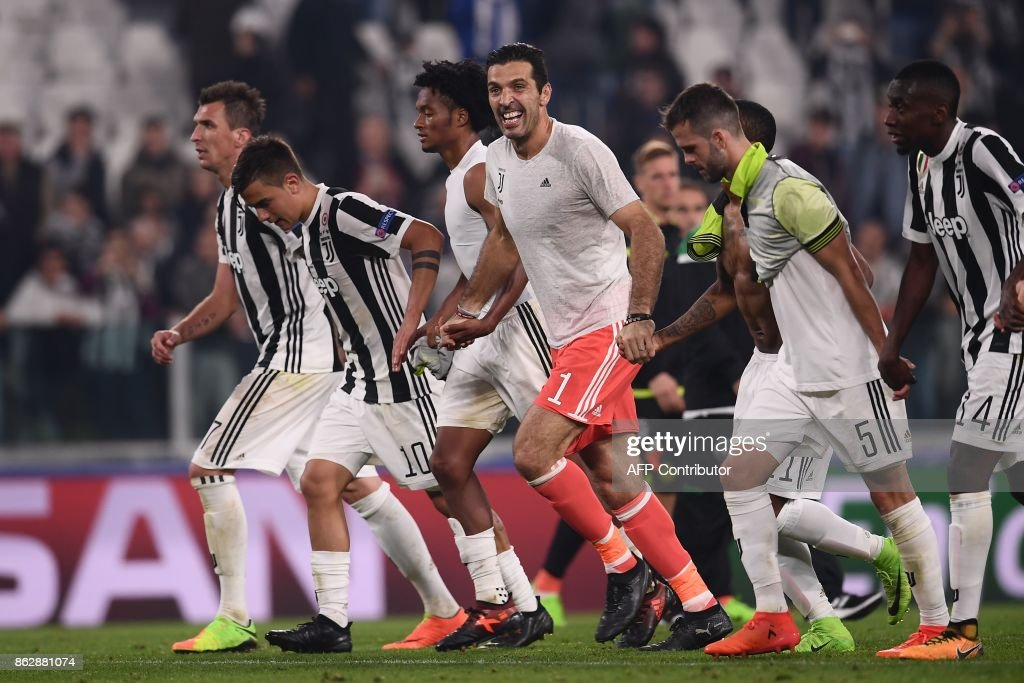 Juventus' goalkeeper from Italy Gianluigi Buffon (C) celebrates with teammates at the end of the UEFA Champions League Group D football match Juventus vs Sporting CP at the Juventus stadium on October 17, 2017 in Turin. Juventus won 2-1. / AFP PHOTO / Marco BERTORELLO