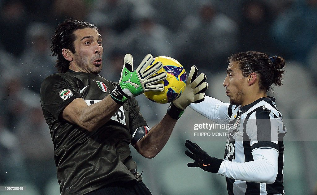 Juventus' goalkeeper Gianluigi Buffon (L) and Uruguayan defender Martin Caceres save the ball against Udinese during their Serie A football match in Turin's Juventus Stadium on January 19, 2013.