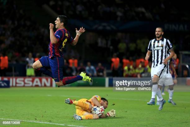 Juventus Goalkeeper Gianluigi Buffon claims the ball from the feet of Barcelona's Luis Suarez