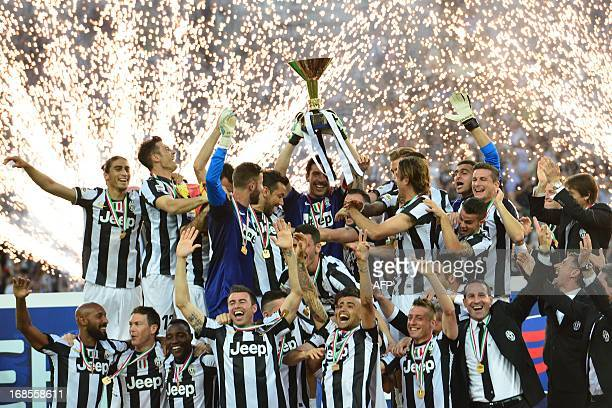 Juventus' goalkeeper Gianluigi Buffon holds the Scudetto the Italian Serie A trophy with teammates during a ceremony after the Italian Serie A...