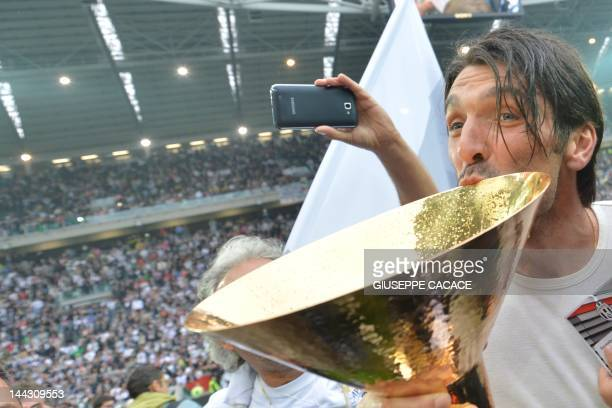 Juventus' goalkeeper Gianluigi Buffon kisses the Italian Serie A football trophy the Scudetto during a ceremony after the team's match against...