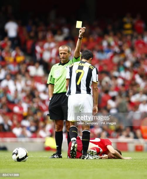 Juventus' Hasan Salihamidzic is shown the yellow card as Hamburg's Ivica Olic lies injured on the floor