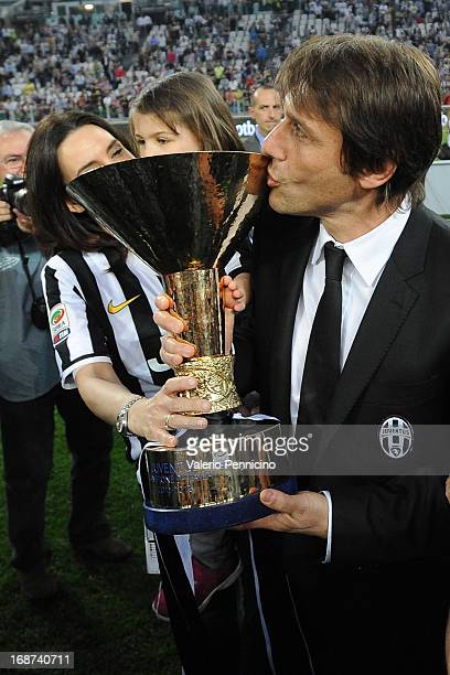 Juventus head coach Antonio Conte celebrates with the Serie A trophy at the end of the Serie A match between Juventus and Cagliari Calcio at Juventus...