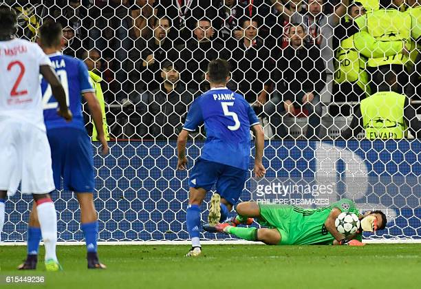 Juventus' Italian goalkeeper Gianluigi Buffon stops a penalty shooted by Lyon's French forward Alexandre Lacazette during the Champions League...