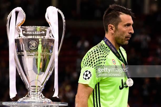 Juventus' Italian goalkeeper Gianluigi Buffon walks past the trophy after Real Madrid won the UEFA Champions League final football match between...