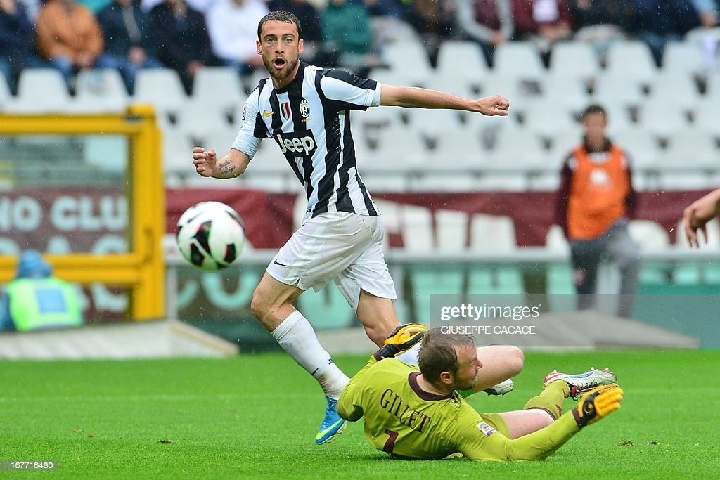 Juventus' Italian midfielder Claudio Marchisio (L) vies for the ball with Torino's French goalkeeper Jean-Francois Gillet during the Italian Serie A football match between Torino and Juventus on April 28, 2013 at the Olympic Stadium in Turin.
