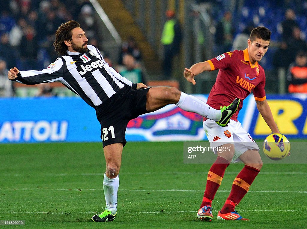Juventus' midfielder Andrea Pirlo vies with AS Roma Argentine forward Erik Lamela (R) during the Italian Serie A football match between AS Roma and Juventus on February 16, 2013 at the Olympic Stadium in Rome.