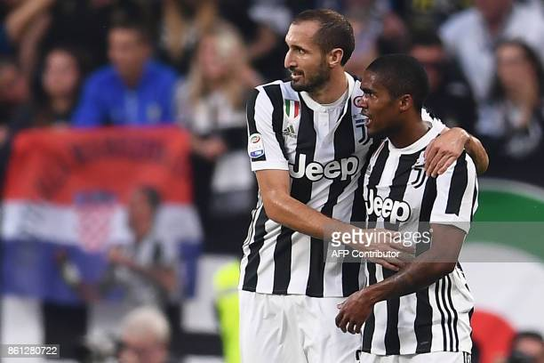 Juventus' midfielder Douglas Costa from Brazil celebrates after scoring with teammate Juventus' defender Giorgio Chiellini during the Italian Serie A...