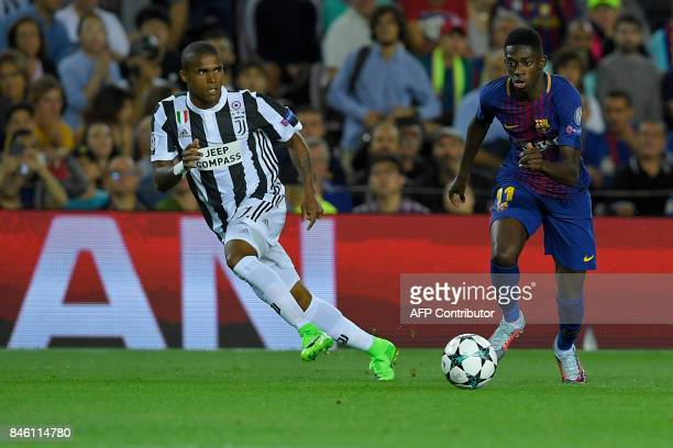 Juventus' midfielder from Brazil Douglas Costa vies with Barcelona's forward from France Ousmane Dembele during the UEFA Champions League Group D...