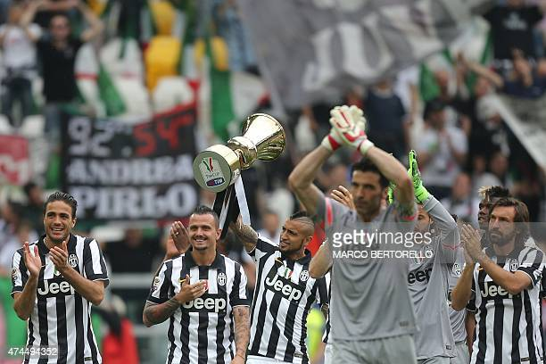 Juventus' midfielder from Chile Arturo Vidal holds the Cup as players present the Tim Cup trophy to their fans prior the Italian Serie A football...