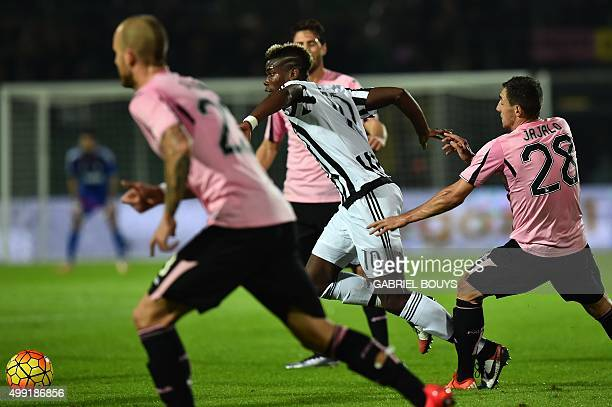 Juventus' midfielder from France Paul Pogba vies with Palermo's defenders during the Italian Serie A football match between Palermo and Juventus on...
