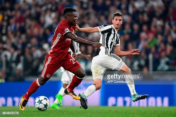 Juventus' midfielder from Uruguay Rodrigo Bentancur vies with Olympiacos' Nigerian Defender Emmanuel Emenike during the UEFA Champion's League Group...