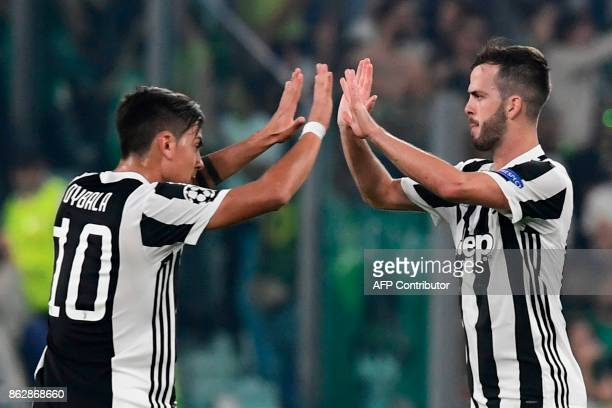 Juventus midfielder Miralem Pjanic celebrates with Juventus' forward from Argentina Paulo Dybala after scoring during the UEFA Champions League Group...
