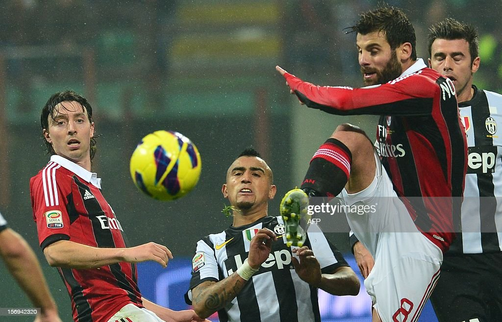 Juventus' midfielder of Chile Arturo Vidal (C) fights for the ball with AC Milan's midfielder Antonio Nocerino (R) and AC Milan's midfielder Riccardo Montolivo during the Italian serie A football match between AC Milan and Juventus on November 25, 2012 at the San Siro stadium in Milan. AFP PHOTO / GIUSEPPE CACACE