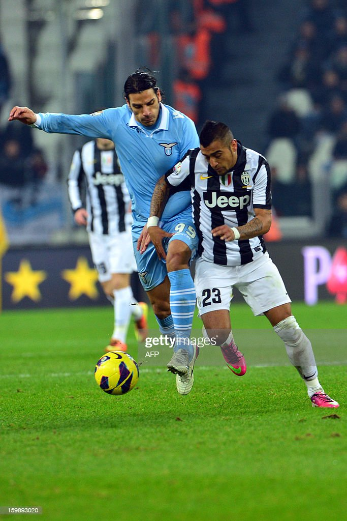 Juventus' midfielder of Chile Arturo Vidal (R) vies with Lazio's forward Sergio Floccari during their TIM CUP football match between Juventus and Lazio at the 'Juventus Stadium' in Turin on January 22, 2013.
