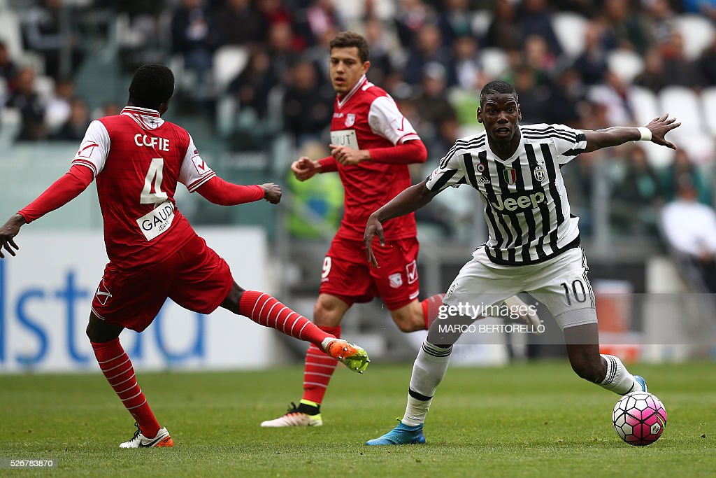 Juventus' midfielder Paul Pogba from France (R) fights for the ball with Carpi's midfielder Isaac Cofie from Ghana during the Italian Serie A football match Juventus Vs Carpi on May 1, 2016 at the 'Juventus Stadium' in Turin. / AFP / MARCO