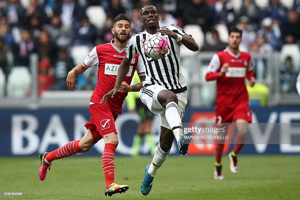 Juventus' midfielder Paul Pogba from France (R) fights for the ball with Carpi's midfielder Marco Crimi during the Italian Serie A football match Juventus Vs Carpi on May 1, 2016 at the 'Juventus Stadium' in Turin. / AFP / MARCO