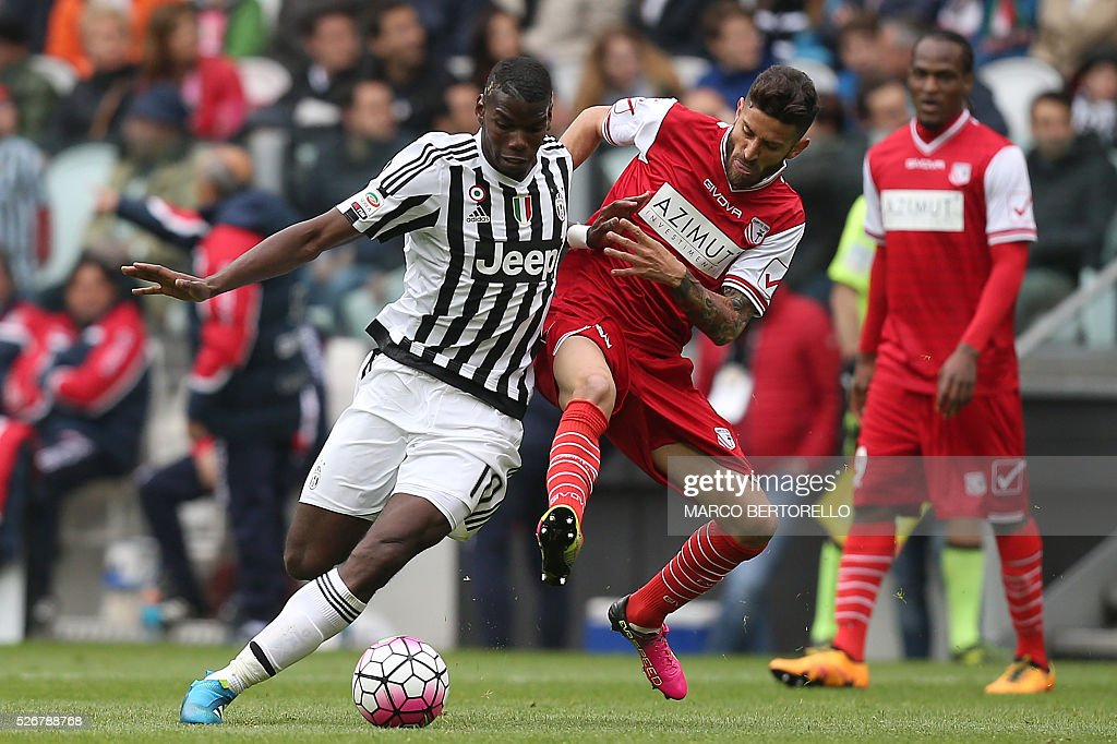 Juventus' midfielder Paul Pogba from France fights for the ball with Carpi's midfielder Marco Crimi during the Italian Serie A football match Juventus Vs Carpi on May 1, 2016 at the 'Juventus Stadium' in Turin. / AFP / MARCO