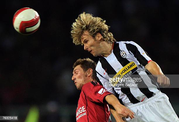 Juventus midfielder Pavel Nedved of the Czeck Republic jumps for the ball with Livorno's midfielder Massimo Loviso their 'Serie A' match at Comunale...
