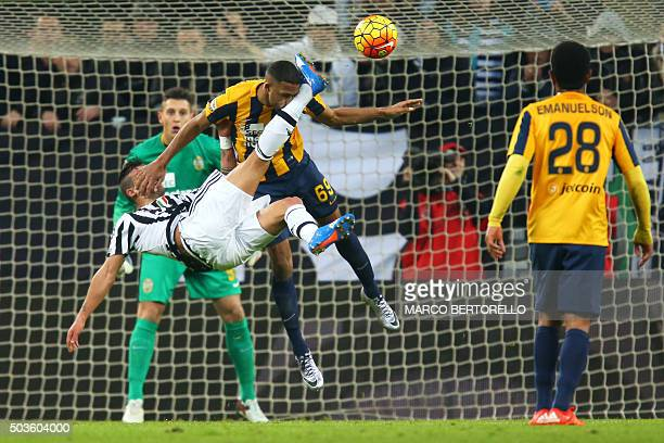 TOPSHOT Juventus' midfielder Stefano Sturaro fights for the ball with Hellas Verona's defender Samuel Souprayen from France during the Italian Serie...