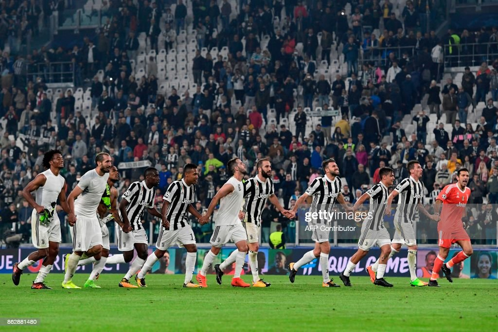 Juventus' players celebrate at the end of the UEFA Champions League Group D football match Juventus vs Sporting CP at the Juventus stadium on October 17, 2017 in Turin. Juventus won 2-1. / AFP PHOTO / Miguel MEDINA