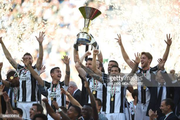 TOPSHOT Juventus' players celebrate with the trophy after winning the Italian Serie A football match Juventus vs Crotone and the 'Scudetto' at the...