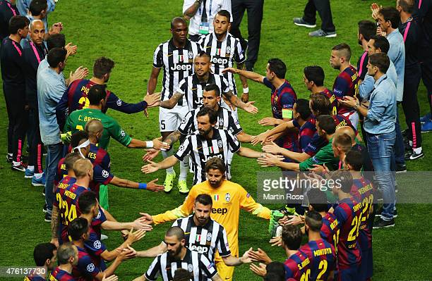 Juventus players shake hands with Barcelona players as they walk to collect their runners up medals during the UEFA Champions League Final between...