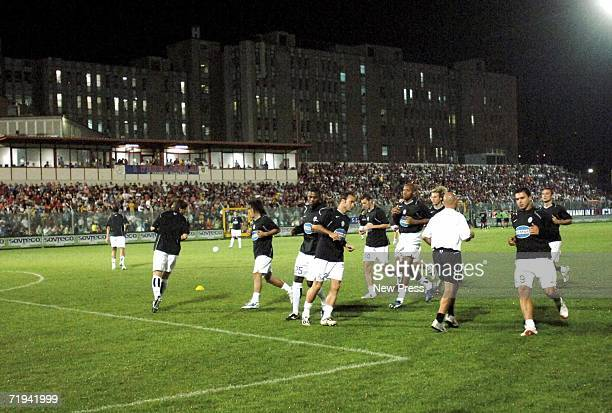 Juventus players warm up before the Serie B match against Crotone as the Crotone hospital rises in the background at Ezio Scida stadium September 19...