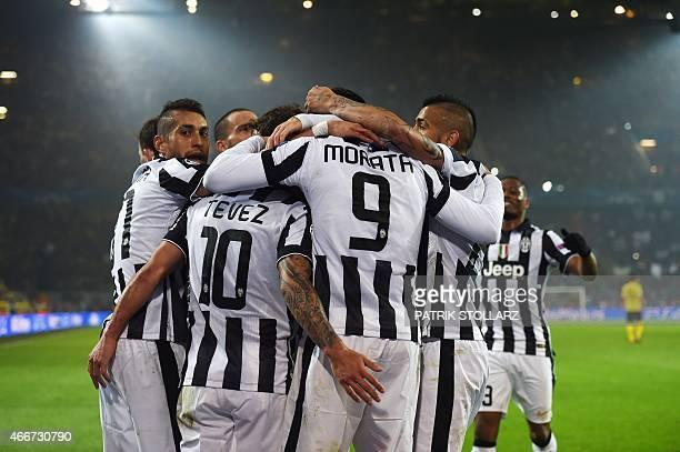 Juventus' Spanish forward Alvaro Morata celebrates scoring with teammates during the Round of 16 secondleg UEFA Champions League football match...