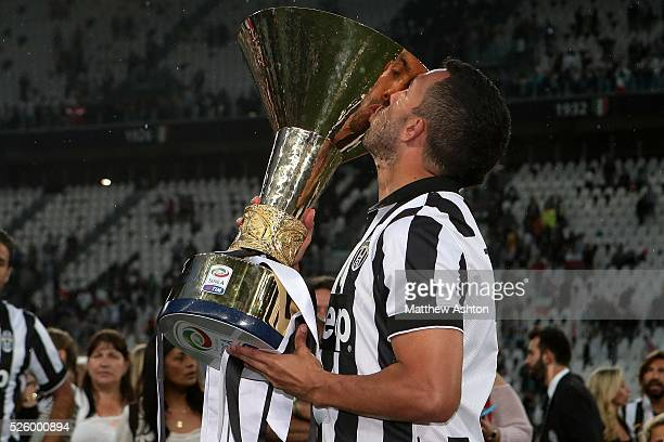 Juventus striker Carlos Tevez celebrates winning Serie A with the scudetto trophy
