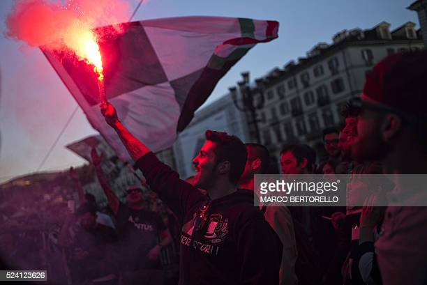 Juventus supporters celebrate after their football club won the Italian Serie A 'Scudetto' in Piazza San Carlo in Turin on April 25 2016 Defending...