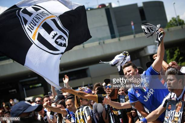 Juventus' supporters wave flags and scarfs as players arrive at the Turin Airport on June 4 a day after the UEFA Champions League final against Real...