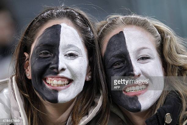 Juventus' supporters wearing the colors of their team pose before the start of the UEFA Europa League football match Juventus vs Fiorentina on March...