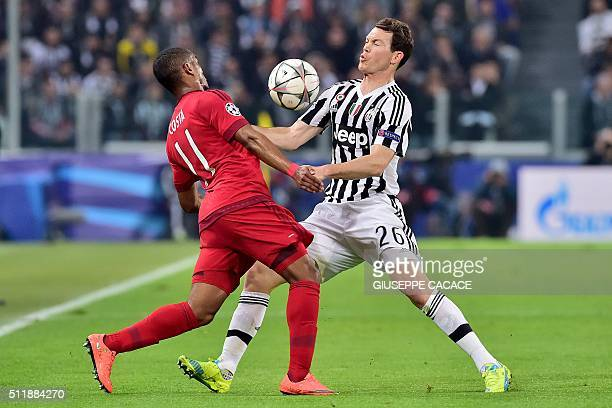 Juventus' Swiss defender Stephan Lichtsteiner challenges Bayern Munich's Brazilian midfielder Douglas Costa during the UEFA Champions League round of...