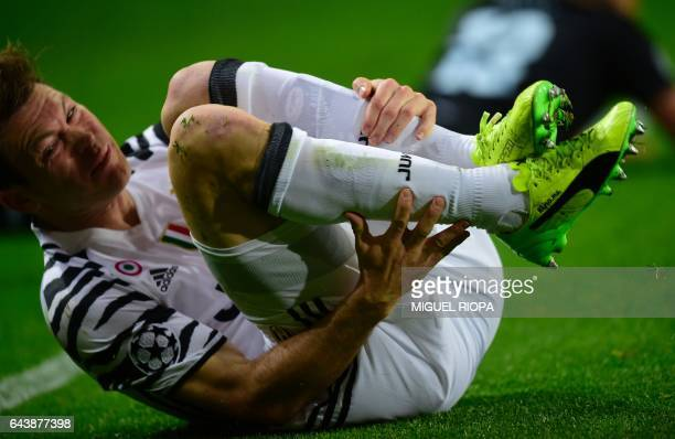 Juventus' Swiss defender Stephan Lichtsteiner falls after being tackled by Porto's Brazilian defender Alex Telles during the UEFA Champions League...