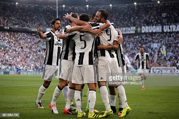 Juventus' teammates celebrate after Juventus' Argentinian forward Gonzalo Higuain scored a goal during the Italian Serie A football match between...