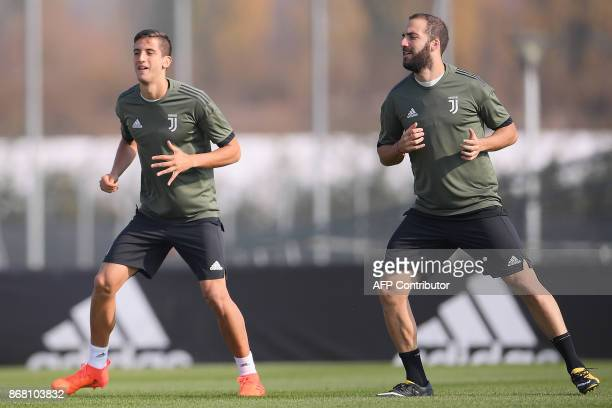 Juventus' Uruguayan midfielder Rodrigo Bentancur and Argentinian forward Gonzalo Higuain take part in a training session on the eve of the UEFA...