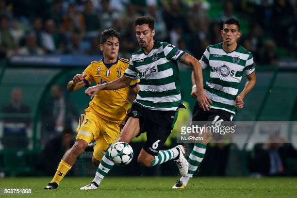 Juventus's forward Paulo Dybala vies for the ball with Sporting's defender Andre Pinto and Sporting's midfielder Rodrigo Battaglia during Champions...
