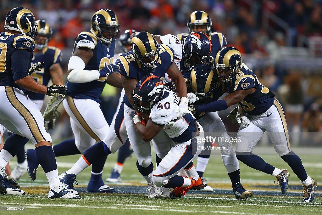 <a gi-track='captionPersonalityLinkClicked' href=/galleries/search?phrase=Juwan+Thompson&family=editorial&specificpeople=7210888 ng-click='$event.stopPropagation()'>Juwan Thompson</a> #40 of the Denver Broncos is tackled by <a gi-track='captionPersonalityLinkClicked' href=/galleries/search?phrase=Alec+Ogletree&family=editorial&specificpeople=7303236 ng-click='$event.stopPropagation()'>Alec Ogletree</a> #52 of the St. Louis Rams and teammates in the fourth quarter at the Edward Jones Dome on November 16, 2014 in St. Louis, Missouri. The Rams beat the Broncos 22-7.