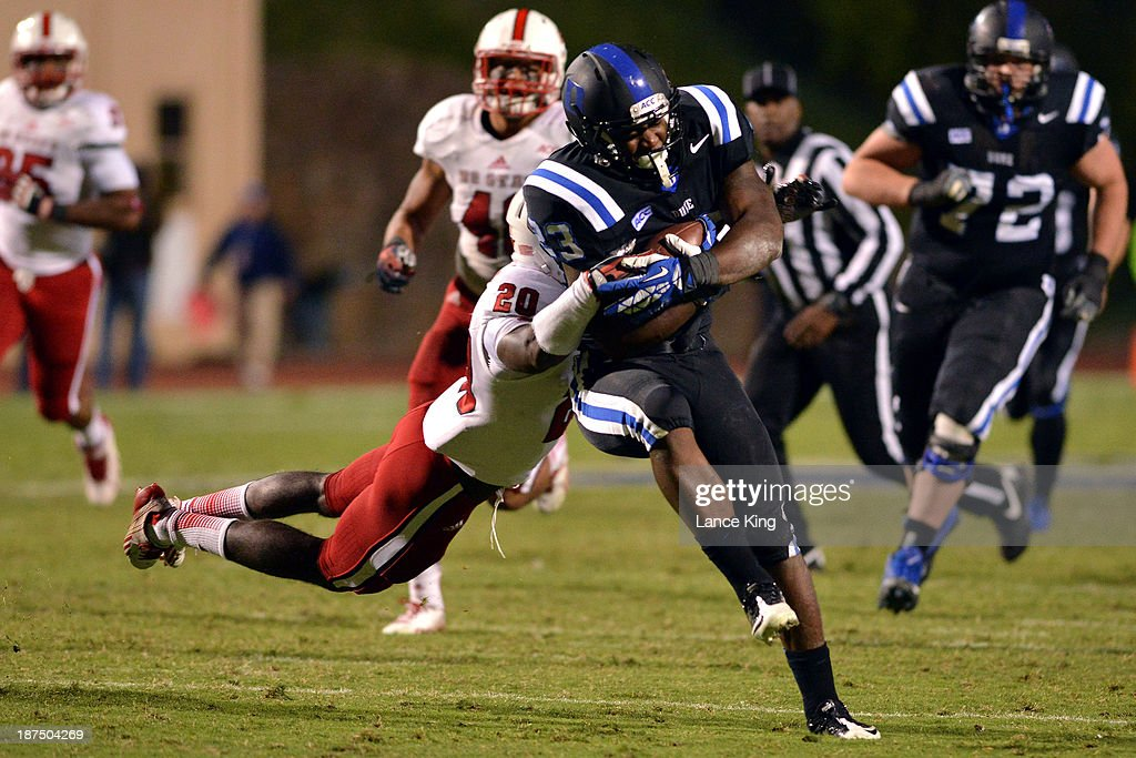 Juwan Thompson #23 of the Duke Blue Devils avoids a tackle from Hakim Jones #20 of the North Carolina State Wolfpack at Wallace Wade Stadium on November 9, 2013 in Durham, North Carolina. Duke defeated NC State 38-20.
