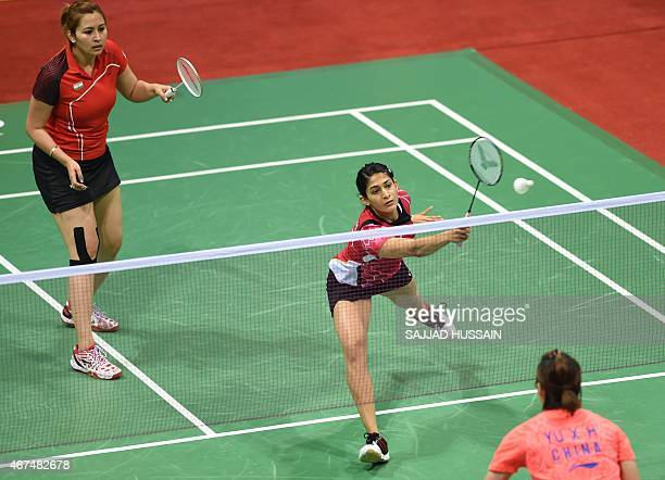 Jwala Gutta look on as Ashwini Ponnappa of India returns a shot to Ou Dongi and Xiaohan of China during their women's badminton doubles match at the...