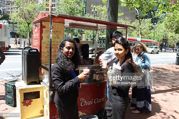 Jyothi Lakshmaiah and Nithya Krishnan take a break from their jobs to enjoy chai from a Chai Cart on Market Street in downtown San Francisco on May...