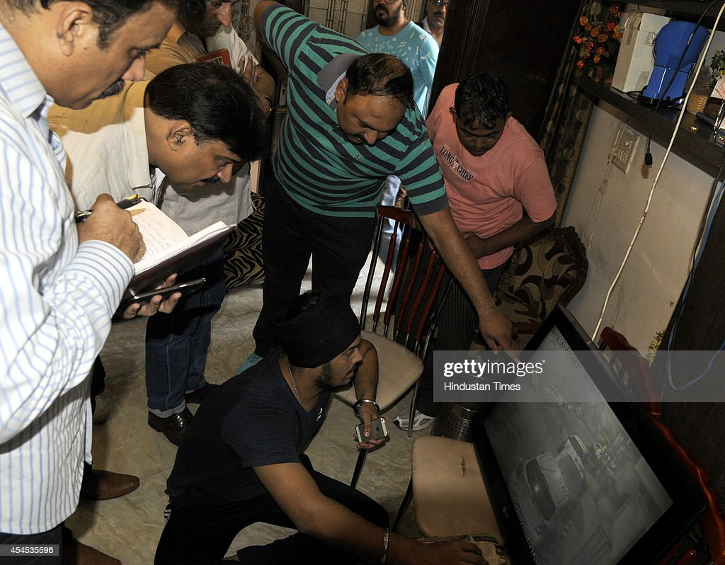 Jyotjeet Singh, son of BJP MLA Jitender Singh Shunty showing the CCTV video footage to the Delhi Police Crime Branch officers, after the BJP MLA was attacked and shot at by an unidentified man at their house in Vivek Vihar on September 3, 2014 in New Delhi, India. The attacker fired three-four times at Shunty but the MLA managed to escape unhurt.