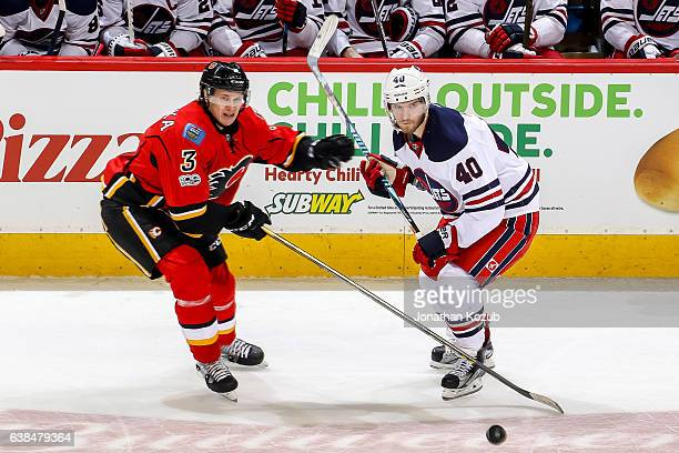 Jyrki Jokipakka of the Calgary Flames and Joel Armia of the Winnipeg Jets keep an eye on the puck during third period action at the MTS Centre on...